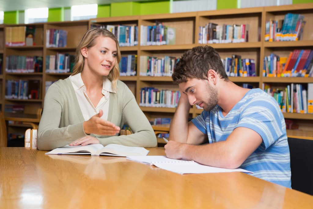 girl tutoring a boy in the library